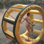 woman in pink tiger stripe swimsuit on water on inflatable wheel