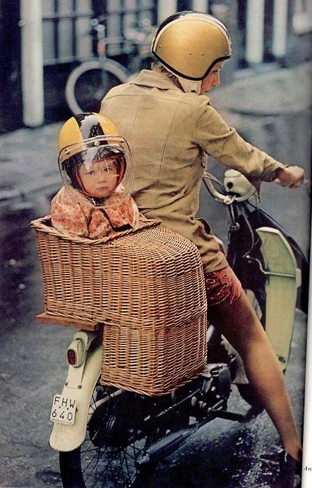 little girl on back of scooter in wicker child seat wearing yellow helmet