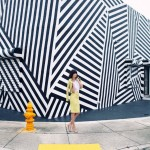 woman in yellow suit in front of stripey building