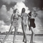 three women on a beach, two in swimsuits, one nude backing camera