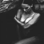 nude woman submerged in water near rocks