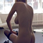 nude woman pulling on stockings