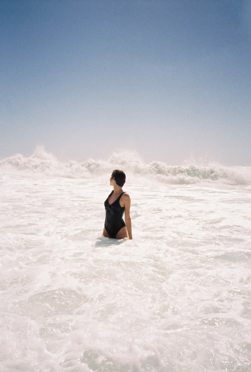 woman in black swimsuit looking at surf