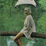 woman with umbrella sitting on log over water