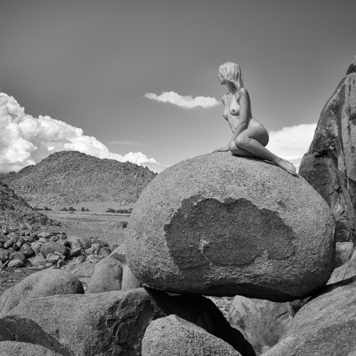 Emmy Grace sits on boulders in the nude