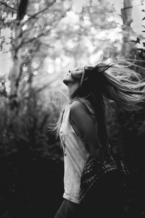 Black & white photo of a young woman tossing her hair back in a woodland area