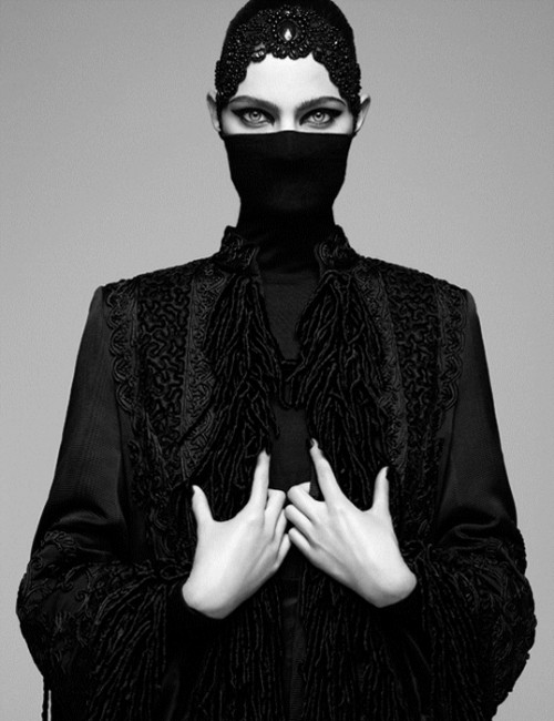 Fashion shoot photograph of a woman covered in black clothing except her hands and eyes