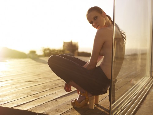 photograph of a topless model crouching on a wooden deck leaning against a glass pane