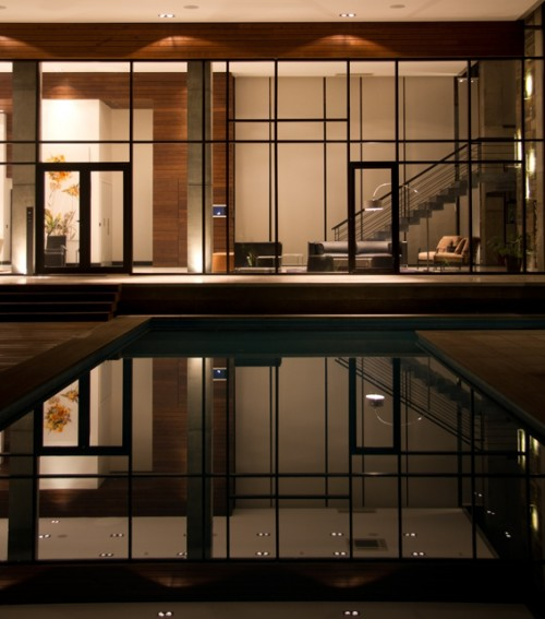 photo of a house at night and its swimming pool