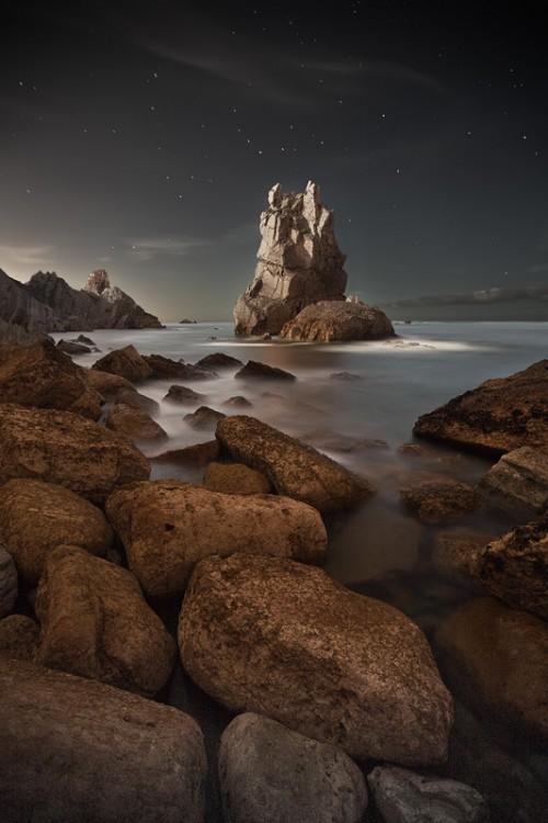 night photograph of a rocky outcrop on a coastline
