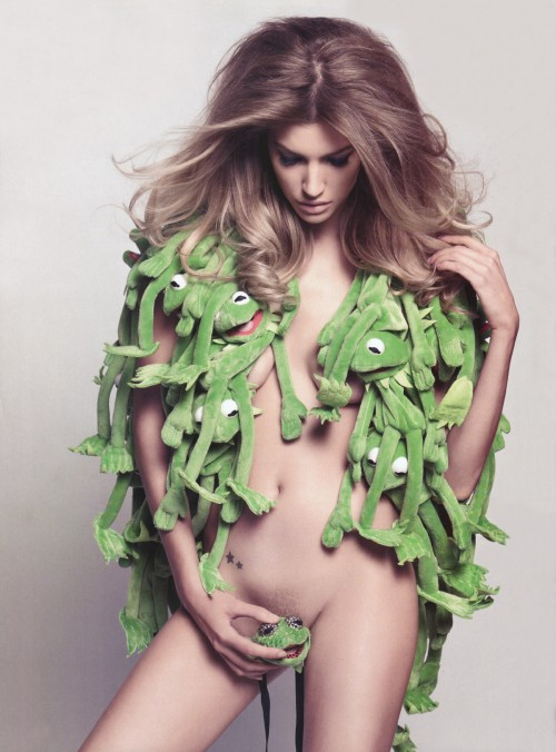 photograph of a nude woman wearing several kermit the frog dolls like a coat
