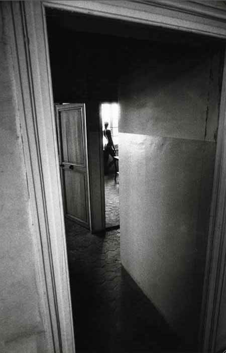 black & white picture of a series of doorways with a silhoutte of a nude