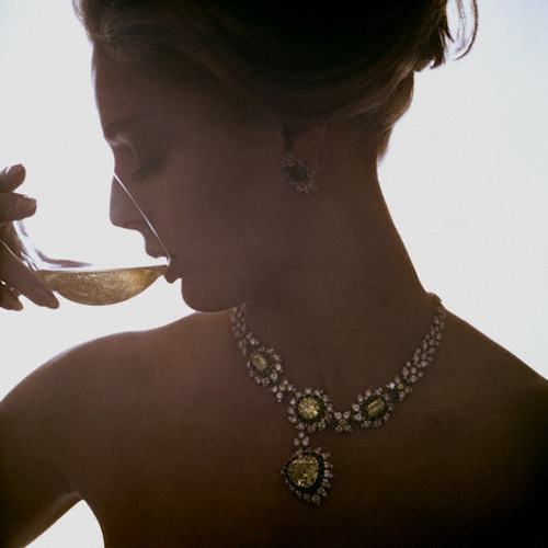 photograph of a woman wearing jewellery drinking wine