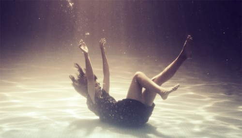 photograph of a woman sinking to the bottom of a swimming pool
