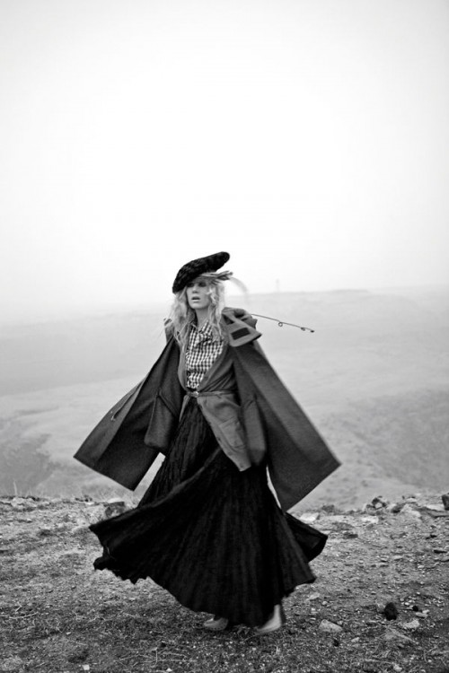 black and white photo of a woman walking on a foggy hillside