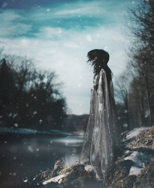 photograph of a woman next to water in a winter woodland