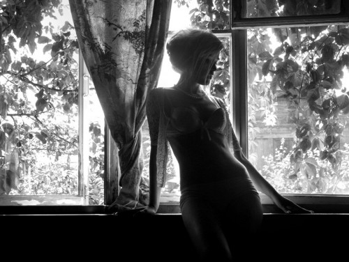 black & white photo of model against window