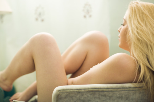 picture of a nude woman sitting in an armchair