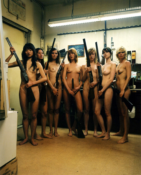 group of nude women holding large guns