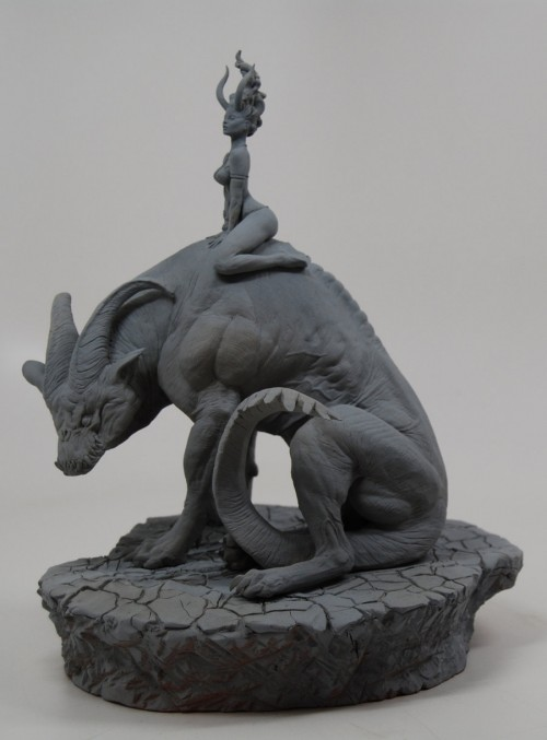 unpainted sculpture of woman sitting on gigantic horned hound-like creature