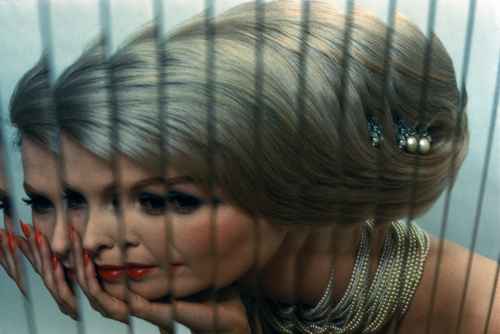 blonde woman with coiffed hair, pearls, red lipstick and nails as reflected through an array of mirror strips