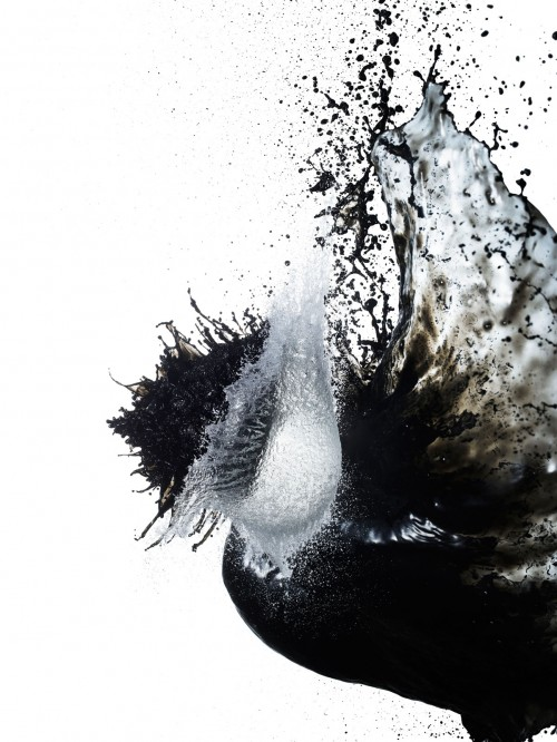 High-speed photograph of a frozen moment as water and black-ink splash into each other