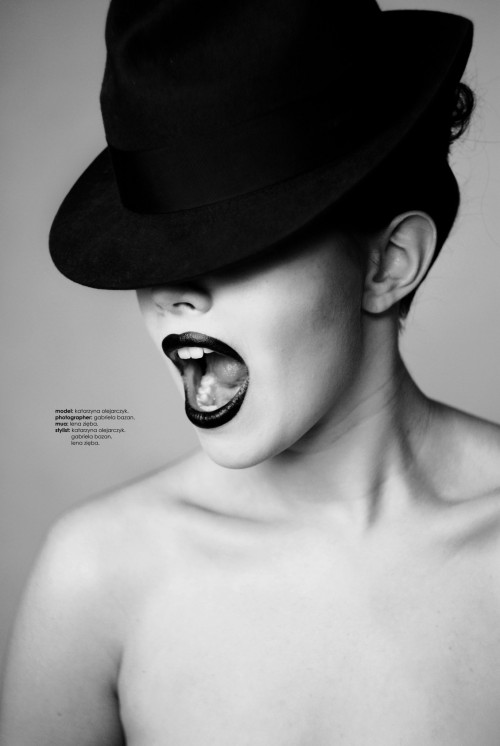 Model with mouth open in a cry and eyes covered by a black hat.