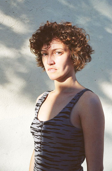 Sunlit portrait of a woman with short curly brown hair wearing a tank-top, against a white wall shadowed by a tree.