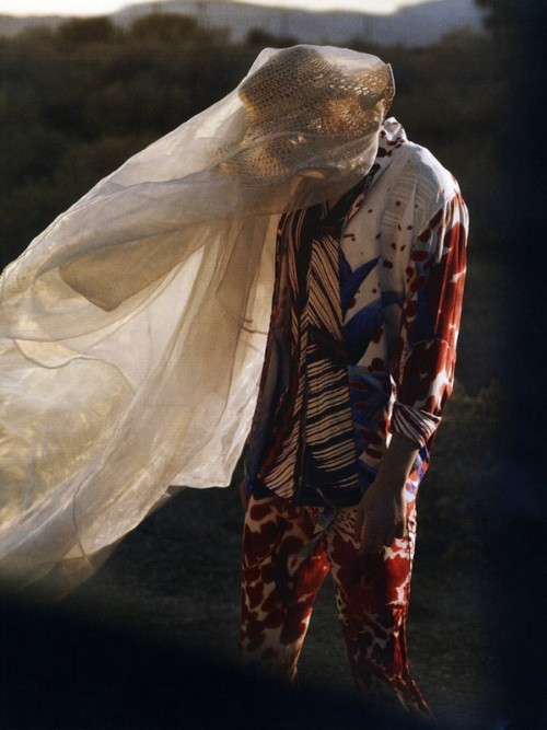 man in colourful clothing with billowing drape on head