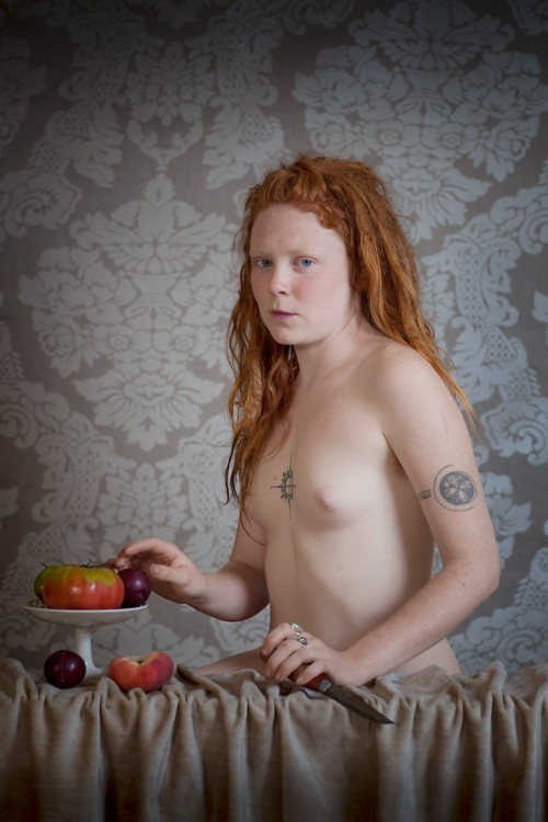 Nude red-heaired tattooed woman holding a knife at a table with patterned wallpaper behind her.