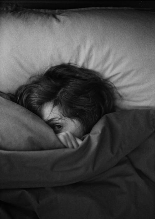 woman peeking through sheets on bed