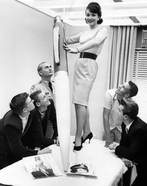 woman holding giant pen standing on table while group of men look up at her