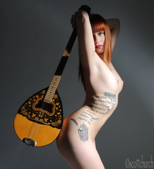 Nude tattooed redhead model holding a banjo behind her back
