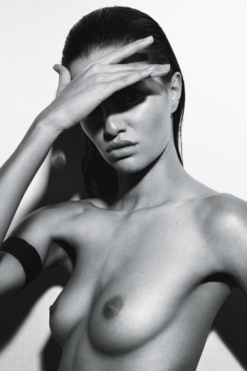 nude woman with black armband sheilding eyes from light