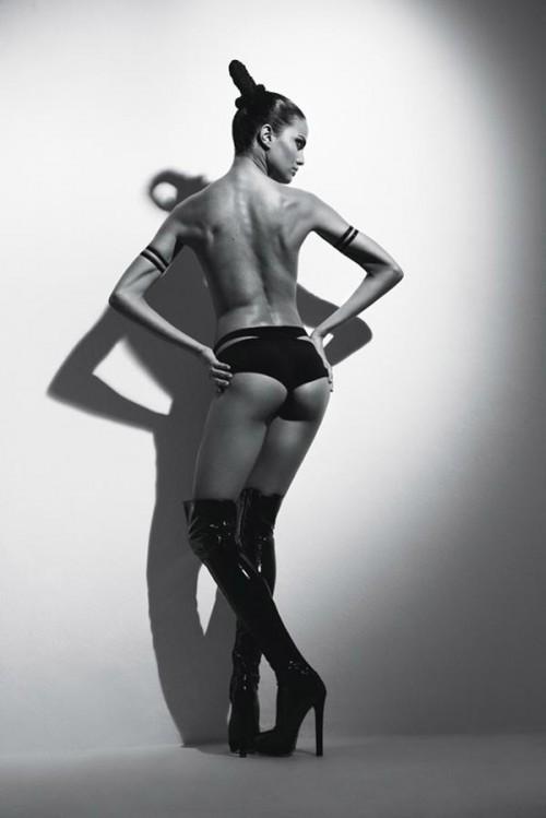 topless woman wearing armbands, panties and long black high heel boots