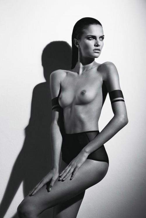 topless woman wearing armbands and panties