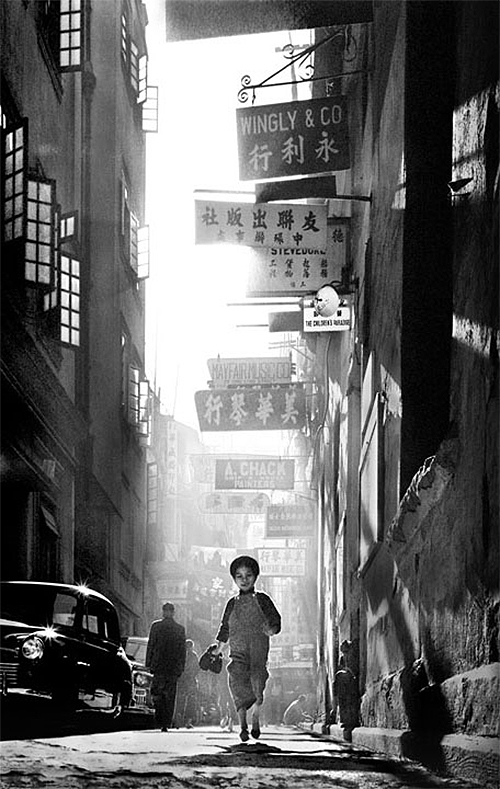 child running down chinese street, by fan ho