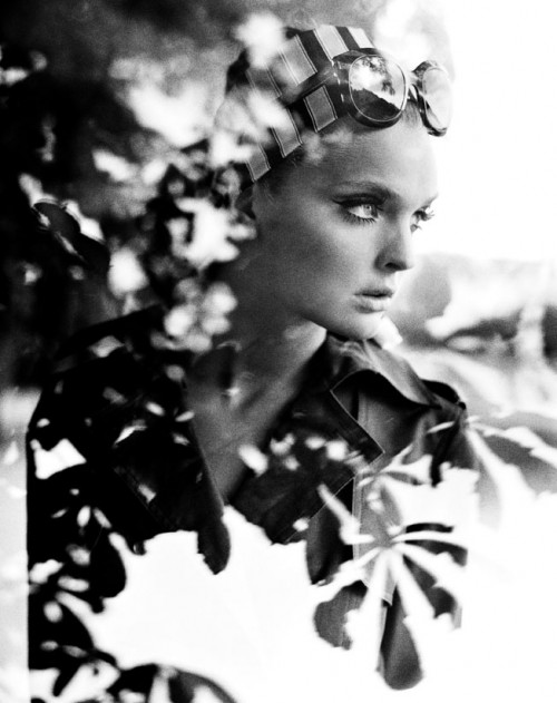 woman with scarf and sunglasses seen through window with reflection of tree leaves