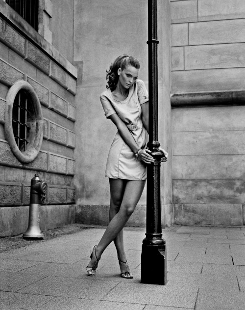 woman standing against lamp post