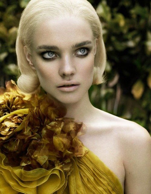 close up of natalia vodianova with blonde hair wearing gauzy gold off-shoulder dress