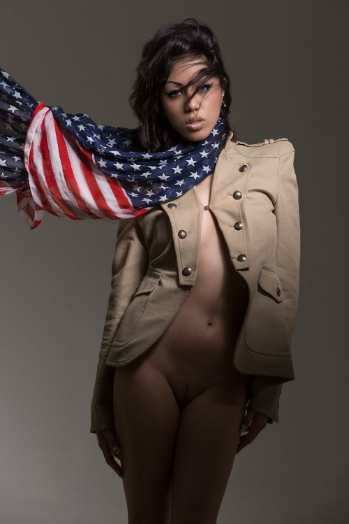 woman in beige pea coat with american flag scarf